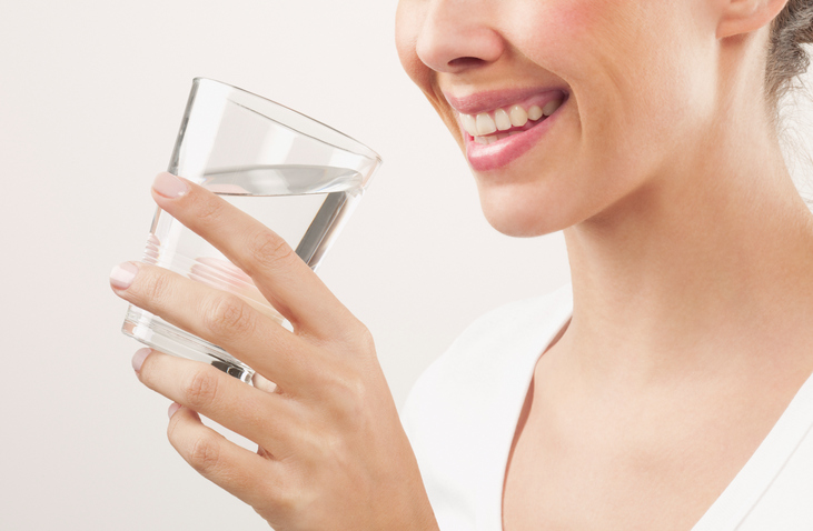 Smiling woman drinking a glass of tap water.