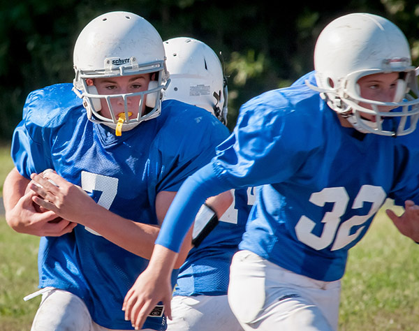 Young football players wearing athletic sports guards.