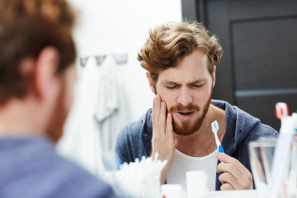Man with sensitive gums brushing his teeth.