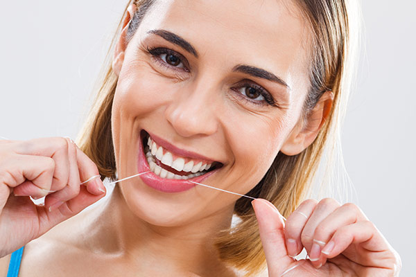A flossing woman with signs of healthy teeth.