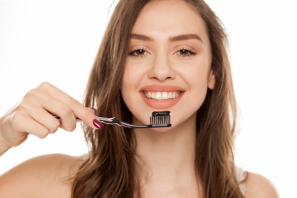 A woman with activated charcoal toothpaste on her toothbrush.
