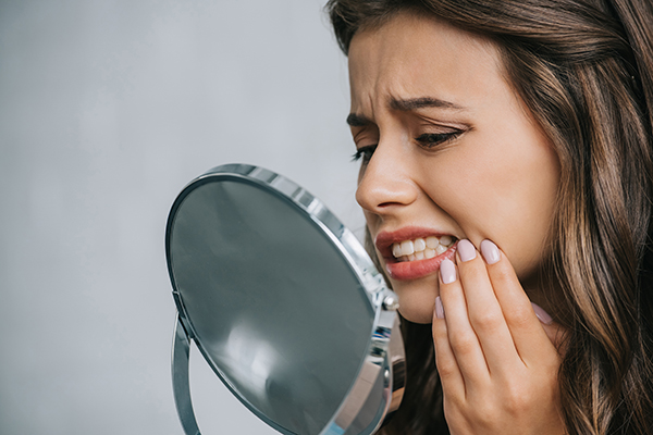 A woman with dental health issues inspecting her mouth with a mirror.