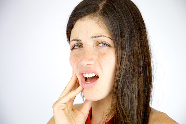 A woman with tooth abscess pain holding her cheek.