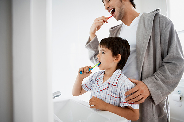 A father showing his son the proper way to brush teeth.