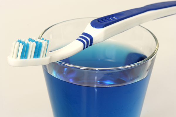 Dental fluoride in a cup beneath a toothbrush