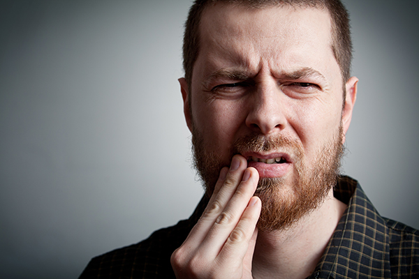 A man holds his mouth in pain, possibly from bleeding gums. Walbridge Dental addresses the cause of bleeding gums.