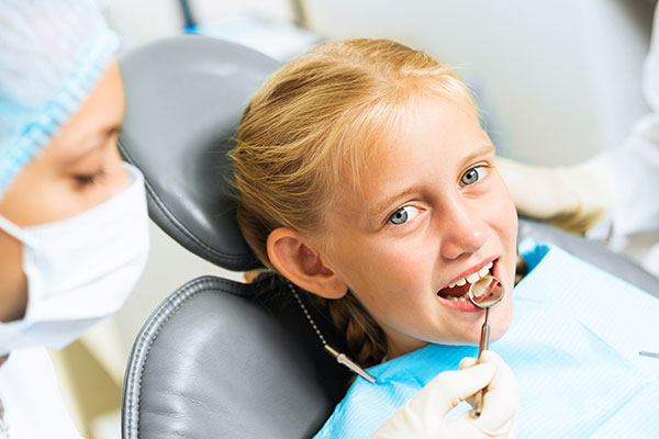 A child at the dentist being checked for tooth decay