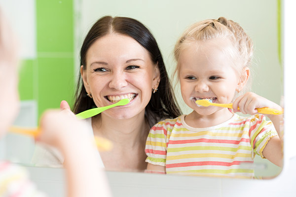 A mother and daughter brushing their teeth together