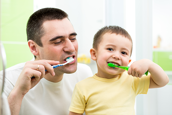 A father and son brushing their teeth together