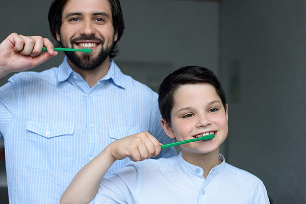 Father and son who appreciate the importance of dental hygiene brushing their teeth