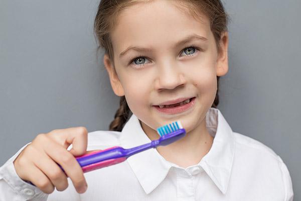 A child brushing their teeth to help keep healthy baby teeth