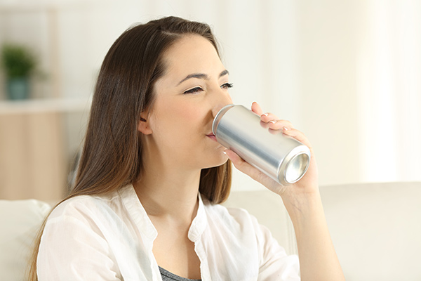 A woman in need of protecting tooth enamel drinking soda