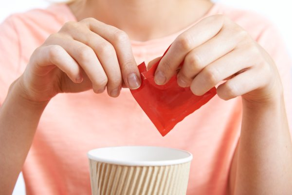A woman tears open a packet of artificial sweetener for her beverage. Do artificial sweeteners cause tooth decay?