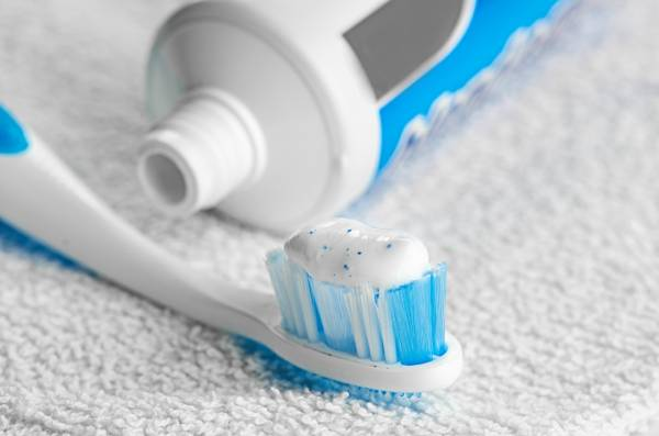 A toothbrush laying on a towel with fluoride toothpaste on it.