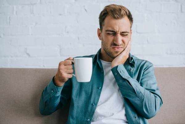 """A man wincing in pain with coffee, wondering """"why are my teeth sensitive?"""""""