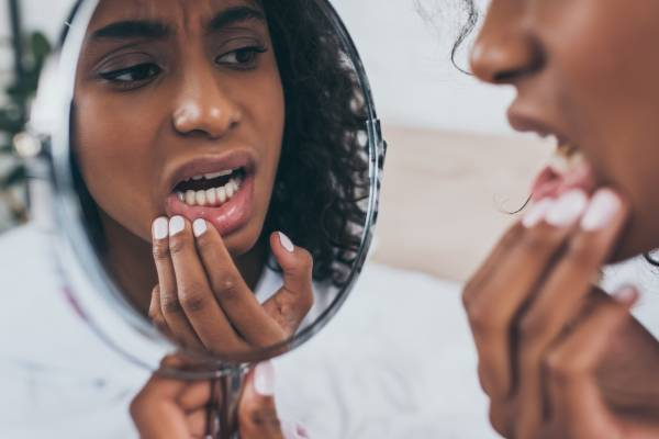 """A worried young woman looks in a mirror at the reflection of her teeth and wonders, """"I chipped my tooth, what should I do?"""""""